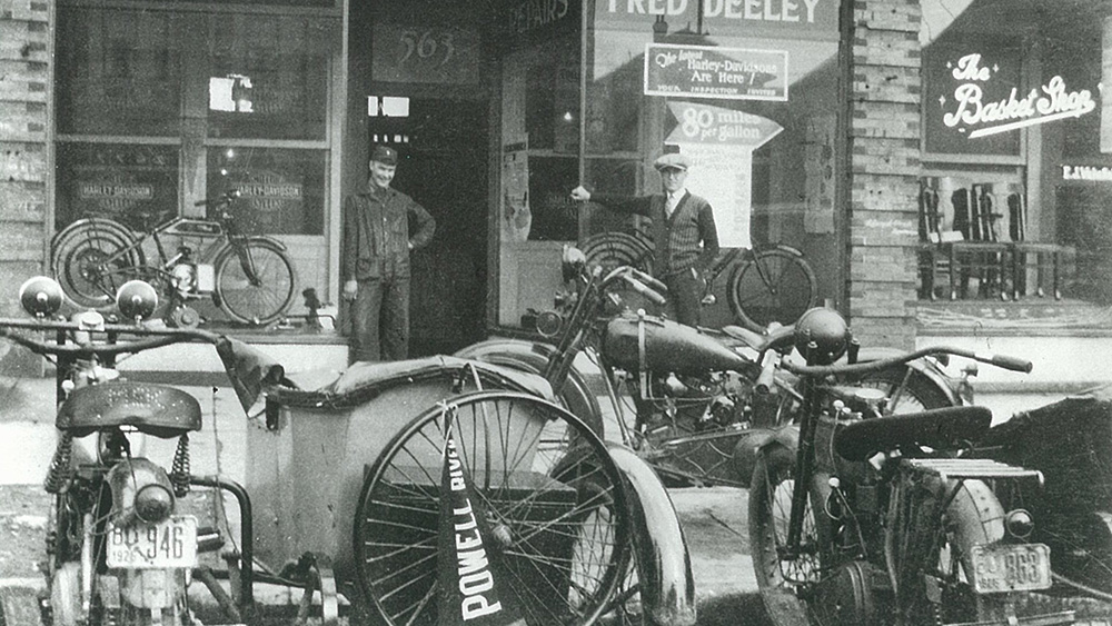 Vintage photo of Deeley Motorcycles showing curbside image with motorcyles and salesmen